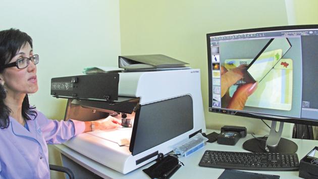 Эксперт. Виктория Куликовская показывает на компараторе, как под углом (свет от зеркала) меняется цвет знака на настоящем документе