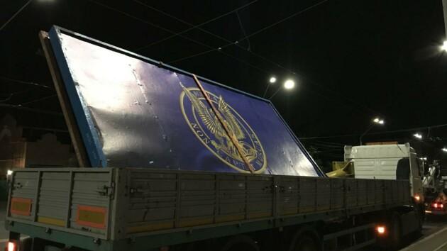 В Киеве коммунальщики сняли щит с эмблемой контрразведки Украины рядом с посольством РФ (фото)