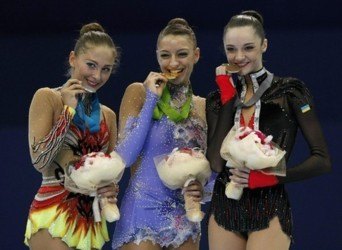 Gold medallist Evgenia Kanaeva (C) of Russia poses with her compatriot silver medallist Daria Kondakova (L) and bronze medallist Anna Bessonova of Ukraine during an awarding ceremony after the individual all-around competition final at the Rhythmic Gymnas