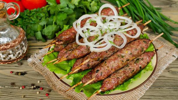 Люля-кебаб часто подают с зеленью и луком Фото: depositphotos.com
