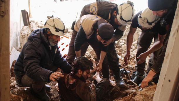 """Члены """"Белых касок"""" спасают пострадавшего из-под обломков. Фото: AFP"""