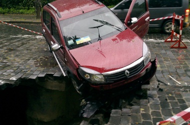 Машина зацепилась задними колесами за люк и нависла над пропастью. Фото: Вконтакте, Оксана Степчук
